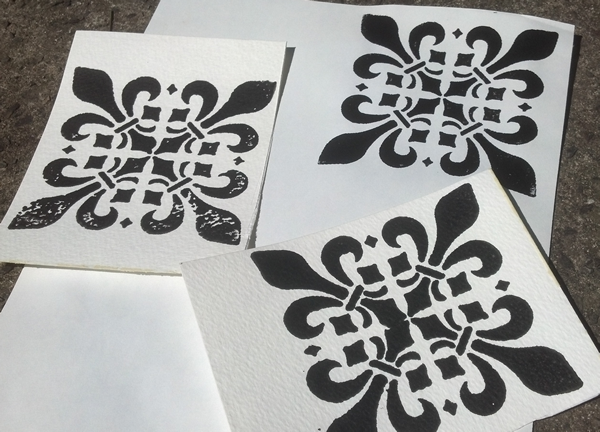 several sheets of paper with screen printed fleury crosses