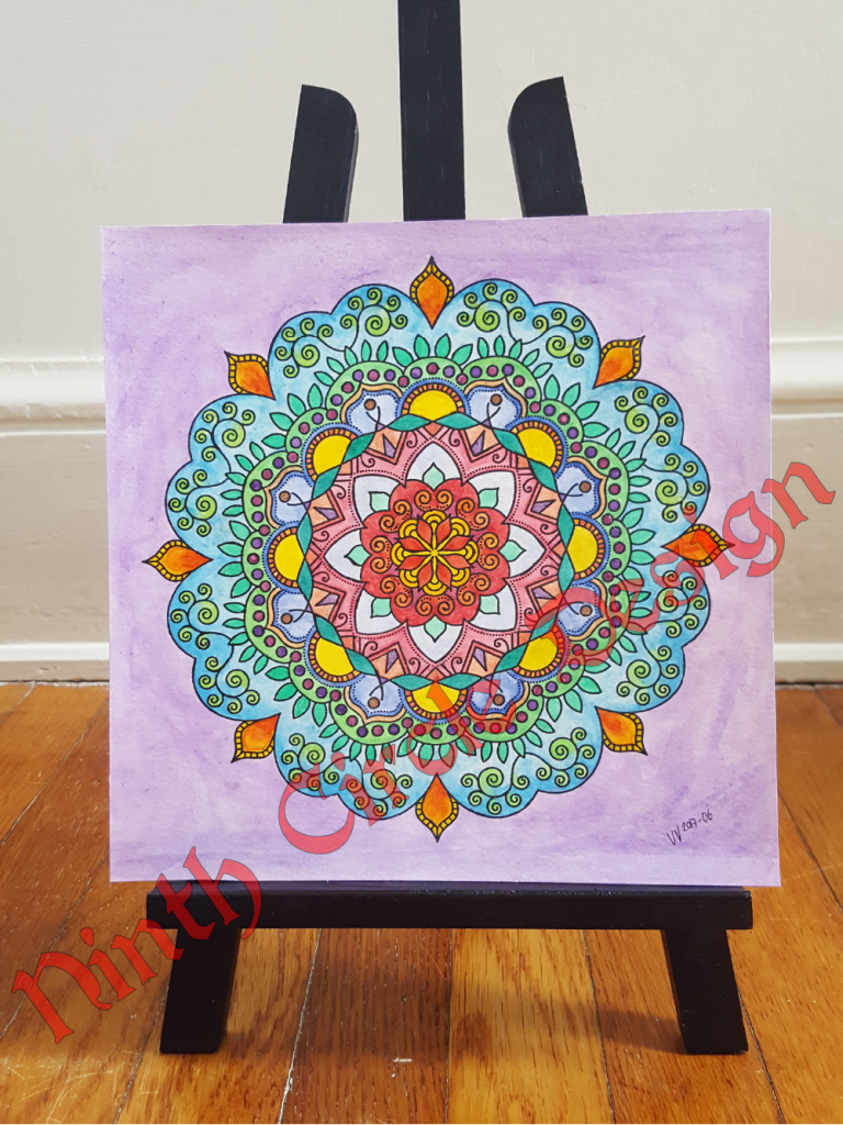 photograph of a square painting on paper, purple background with mandala primarily in blue, green, red, on a small black easel on a wood floor