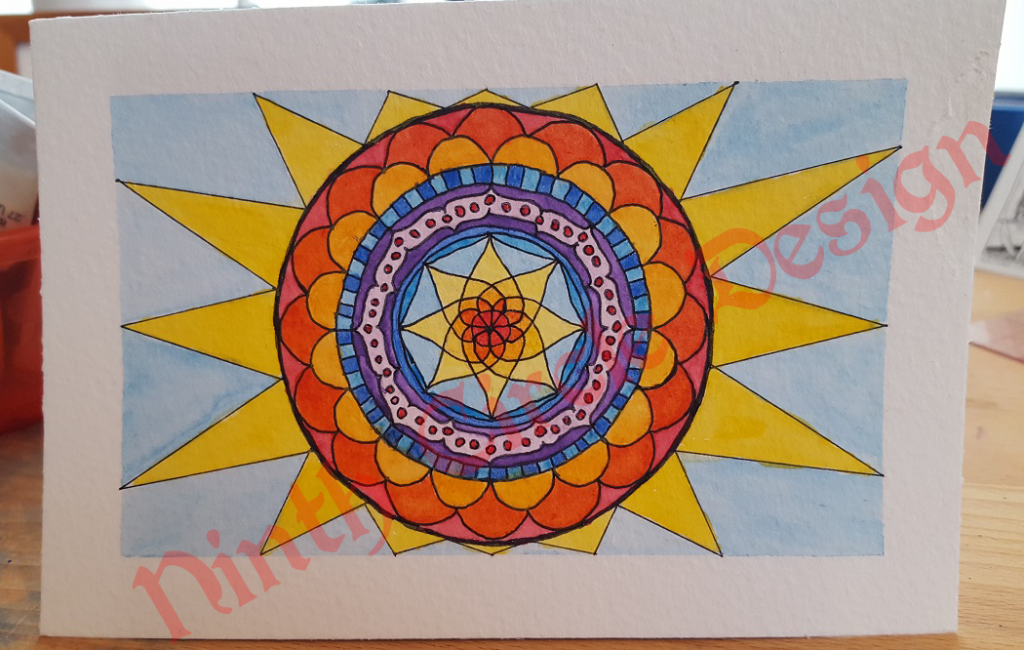 rectangular paper with a mandala shaped to fit the space in yellows and reds, with blues and purple, blue background
