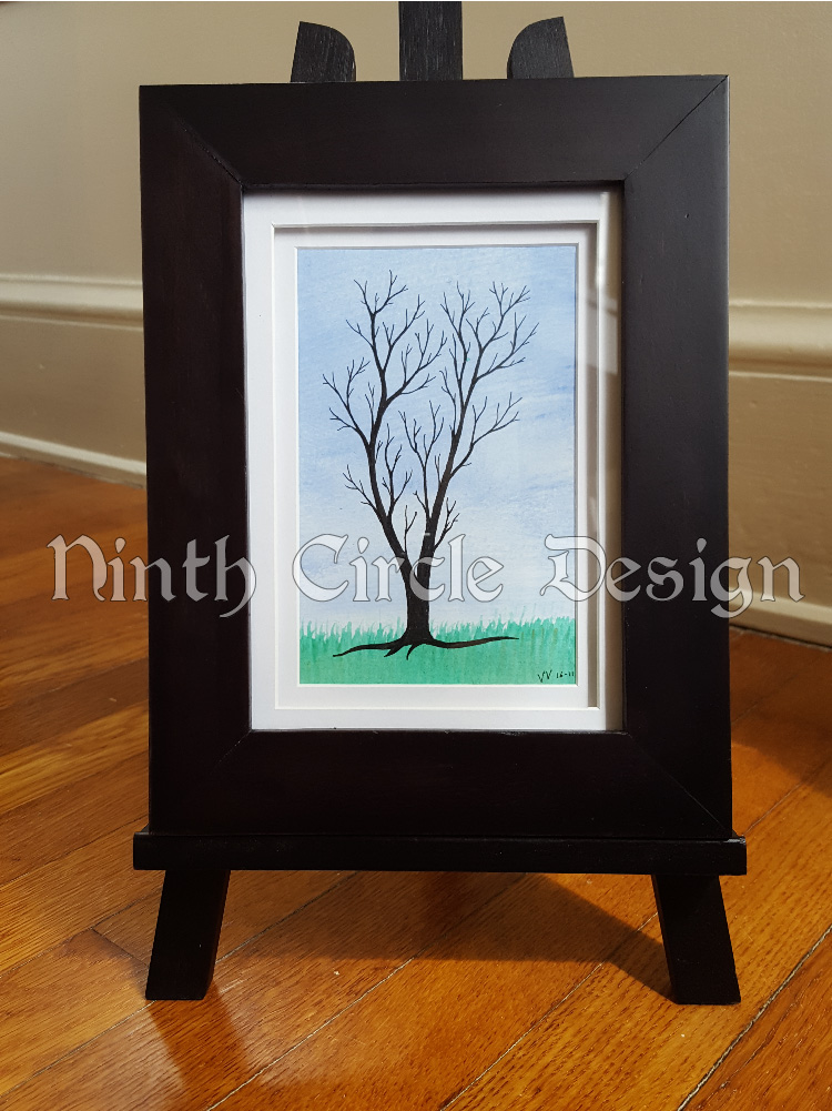 photograph of a framed painting/drawing of a leafless tree (drawn) against a background of blue sky and green grass (painted)