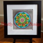 photograph of a mandala in greens and reds within a blue circle and grey background, framed in a black frame, white mat