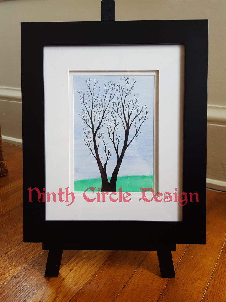 photo of a framed painting with blue sky, green grass, and the silhouette of a leafless tree; frame is black with white mat