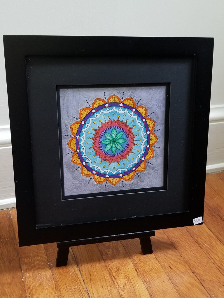 photograph of a framed mandala on a wooden floor near a white wall